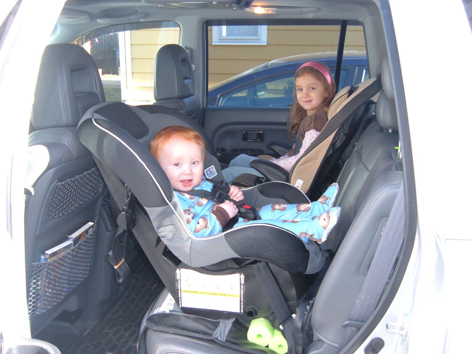Children in back seat of a vehicle in car seats